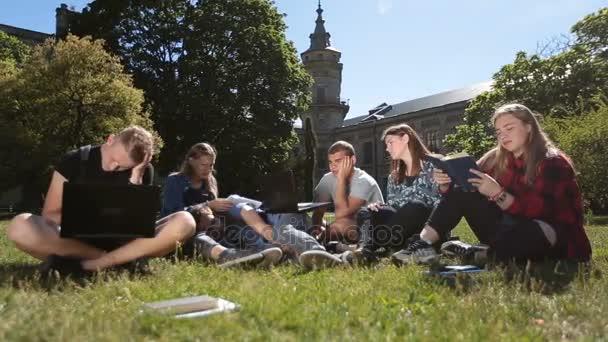 Mladá vyčerpání studentů na akademické půdě trávníku