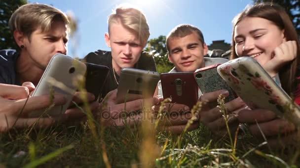 Přátelé v kruhu pomocí smartphone na trávníku parku