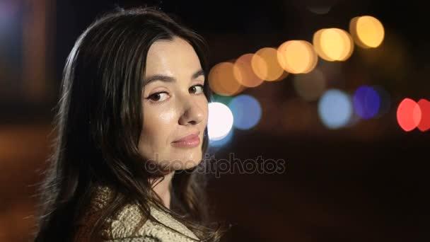 Játékos mosolygó nő flörtöl utcán éjszaka