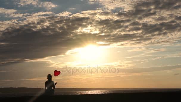 Osamělá žena s balónky-srdce sledovat západ slunce