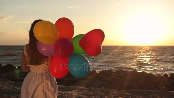 Dívka s barevnými balónky na pláži při západu slunce