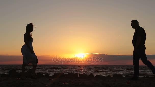 Šťastný pár hospodářství ruce na pláži při západu slunce