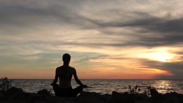 Jóga žena v lotus pose na pláži při západu slunce