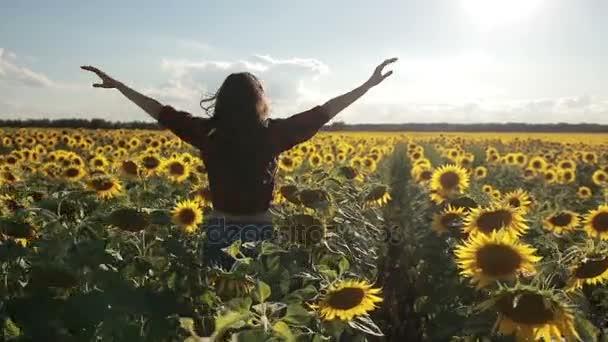 Bezstarostné šťastná žena běží ve slunečnicovém poli