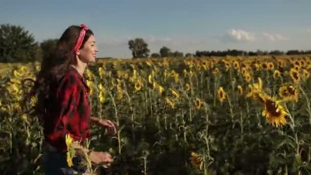 Bezstarostné žena běží přes pole slunečnic