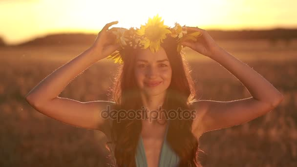 Pretty woman in flower wreath in field at sunset