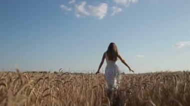 Woman in white dress running through wheat field