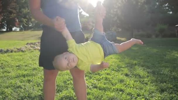 Otče lítací syn batole vzhůru nohama v parku