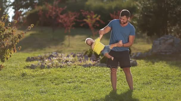 Positive dad playing with toddler son in nature