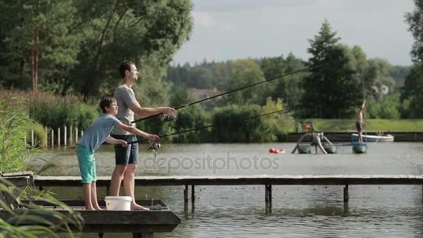 Otec a syn rybaření s pruty na jezeře