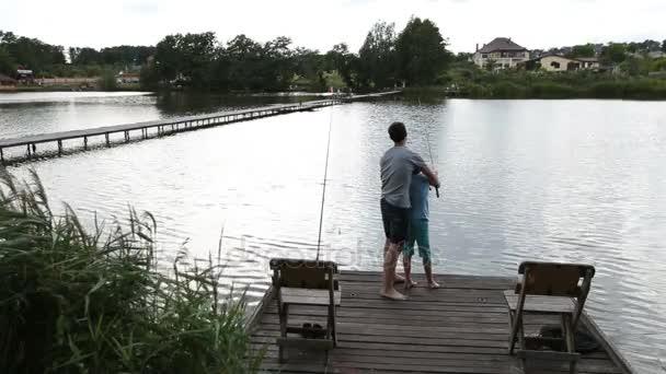 Otec a syn rybaření na klidné jezero v létě