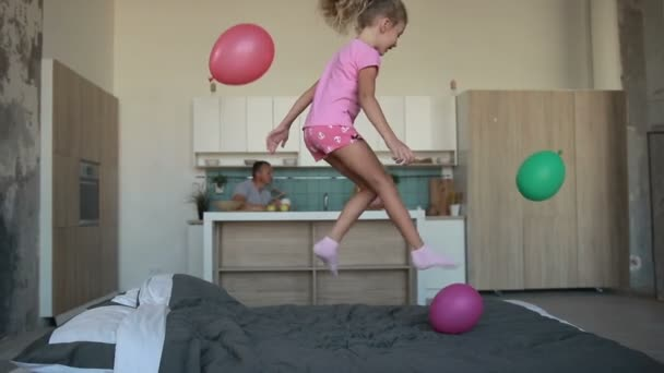 Cute little girl in pajamas jumping on bed