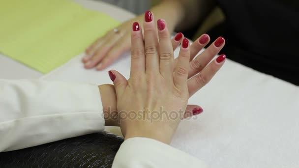 Žena ukazuje její červené gelových v salonu krásy