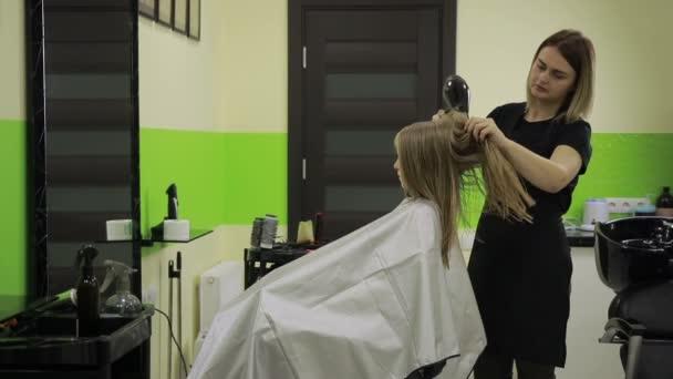 Kadeřník sušení dívky vlasy pomocí fénu