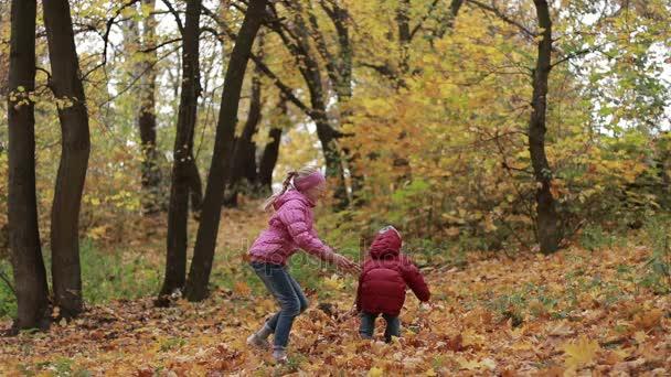 Sourozenci hrát s javorové listy na podzim park