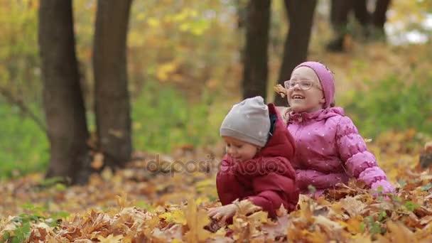 Veselé děti hrají v listech vlasu na podzim