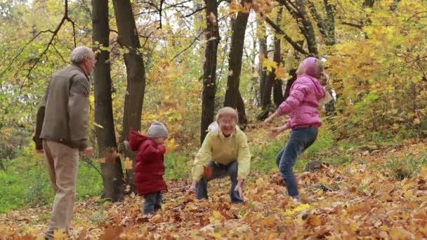 Prarodiče a děti baví na podzim park