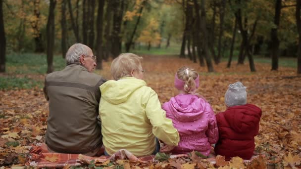 Multi-generation family embracing in autumn park