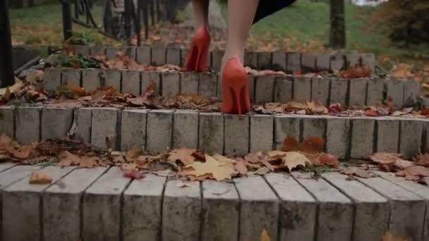 Dáma v oranžové vysoké boty na podpatku chodit nahoře