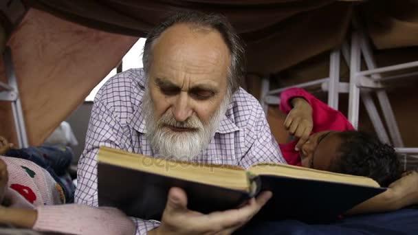 Vousatý věku muž a vnoučaty čtení knihy