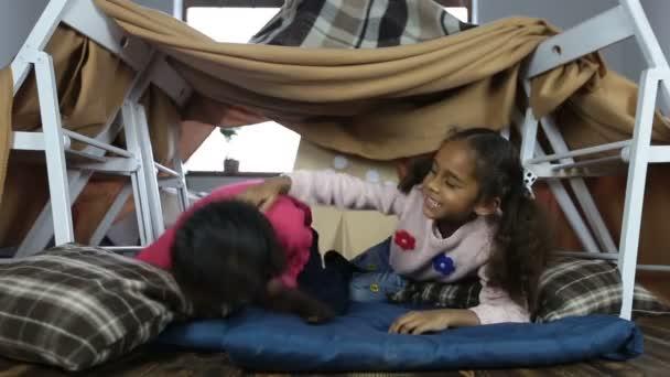 S úsměvem sladké děti hrají společně v obývacím pokoji