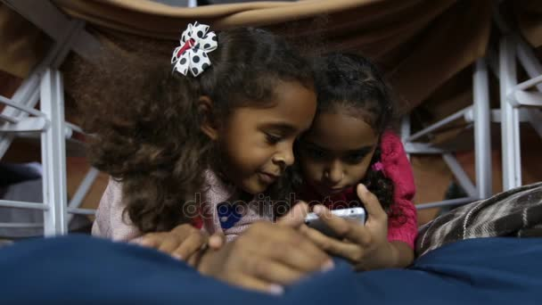Dva usmívající se děti sledují Srandovní obrázky v telefonu