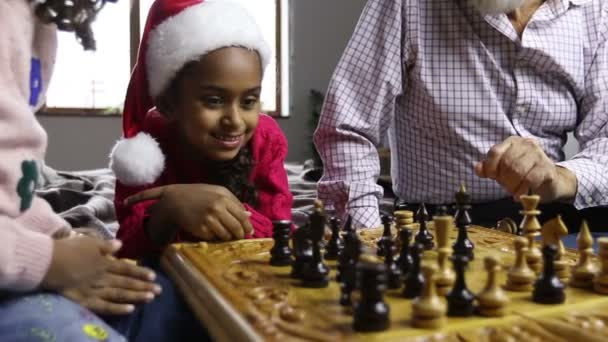 Cute little girl in santa hat watching chess game