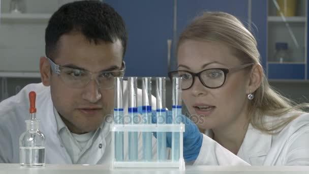 Vědci studují látky do zkumavek v laboratoři
