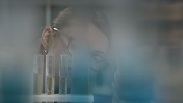 Female scientist examining test tube in lab