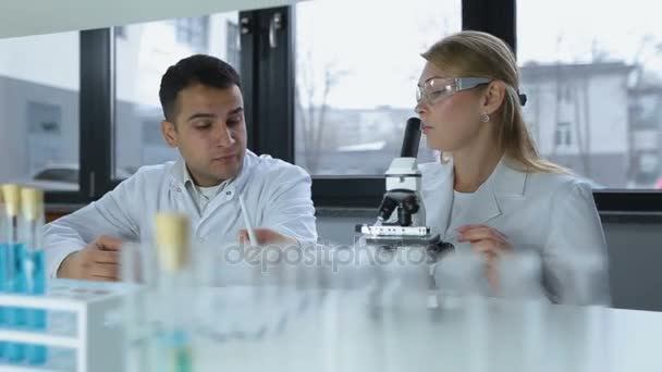 Two focused scientists doing microscope analysis
