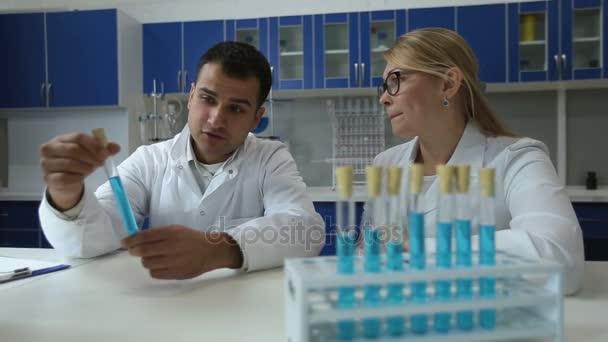 Chemici analýze zkumavky s kapalinou v laboratoři