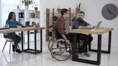 Disabled worker and colleagues working in office