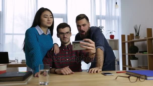 Creative business team taking selfie in the office