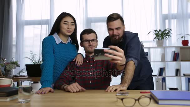 Casual colleagues taking self-portrait in office