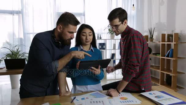 Friendly business team using tablet in office