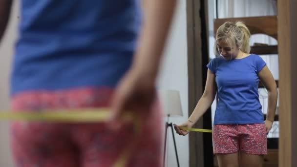 Šťastná žena středního věku měření její boky