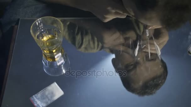 Reflection of male portrait snorting coke line