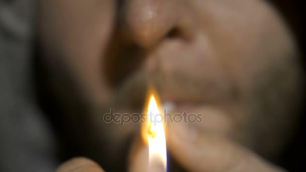 Extreme close-up of man smoking marijuana joint
