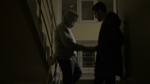 Drug dealer selling drugs to addict on staircase
