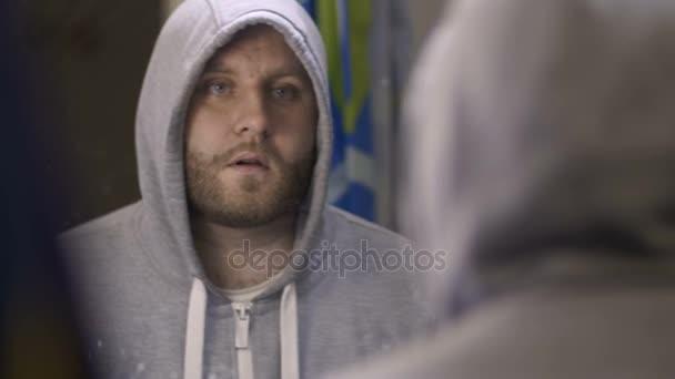 Male addict using breathe spray near the mirror