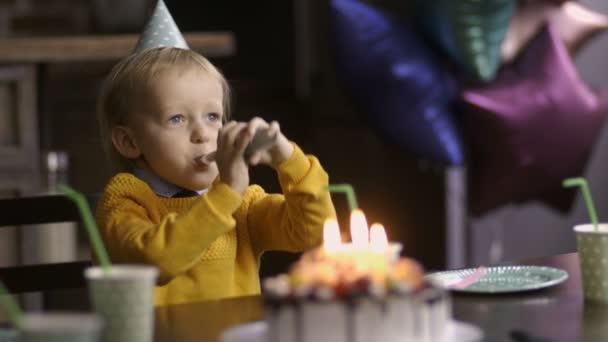 Születésnapján horn fúj asztalnál aranyos totyogó fiú