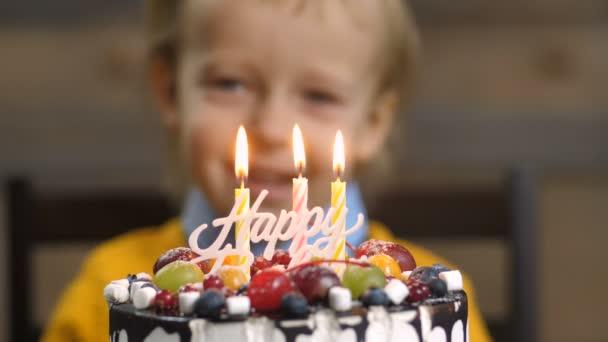 Közeli kép a fiú fúj gyertyákat születésnapi torta