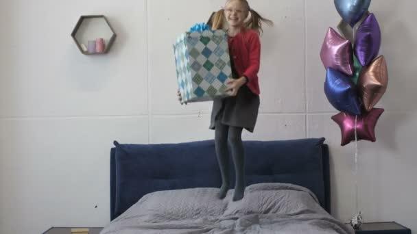 Šťastná dívka skákání na posteli s velký Dárkový box