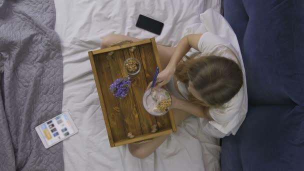 Pohled shora žena jíst zdravou snídani v posteli
