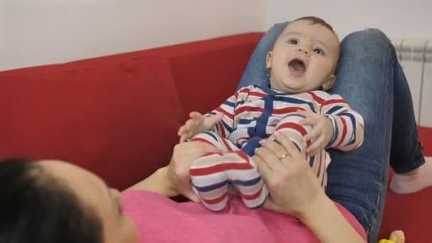 Portrét usmívající se dítě na klíně matky na pohovce