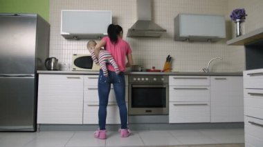 Busy mother cooking in kitchen holding baby son