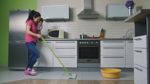 Mutter wischt den Boden und tanzt mit Baby