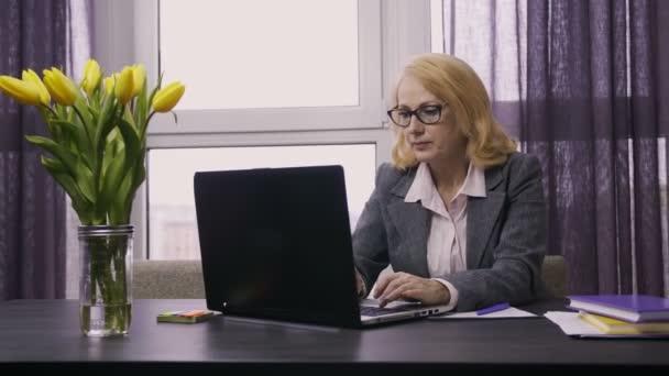 Senior female working on laptop pc at desk