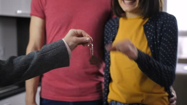 Midsection of happy couple shaking new house key