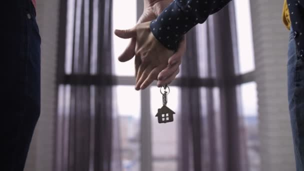 Close-up couple holding hands with new home keys